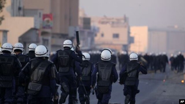Riot police chase Bahraini anti-government protesters in the Shiite Muslim village of Sitra, Bahrain, January 1, 2012.