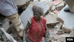 Una mujer haitiana es rescatada de entre los escombros en Puerto Príncipe.