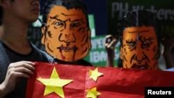 菲律宾学生头戴杜特尔特总统和中国国家主席习近平的漫画脸谱在马尼拉总统府外举行反华示威集会。(2018年11月20日)