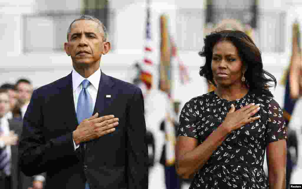 President Barack Obama and First Lady Michelle Obama observe a moment of silence on the 13th anniversary of the 9/11 attacks at the White House, in Washington, Sept. 11, 2014.