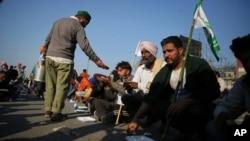 一名印度农民2020年11月28日向参与示威的农民伙伴分发食物。