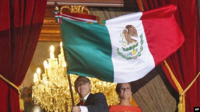 Mexico's President Felipe Calderon waves the national flag next to his wife Margarita Zavala, while thousands of Mexicans celebrate the 201st anniversary of the country's independence from Spain, September 15, 2011.