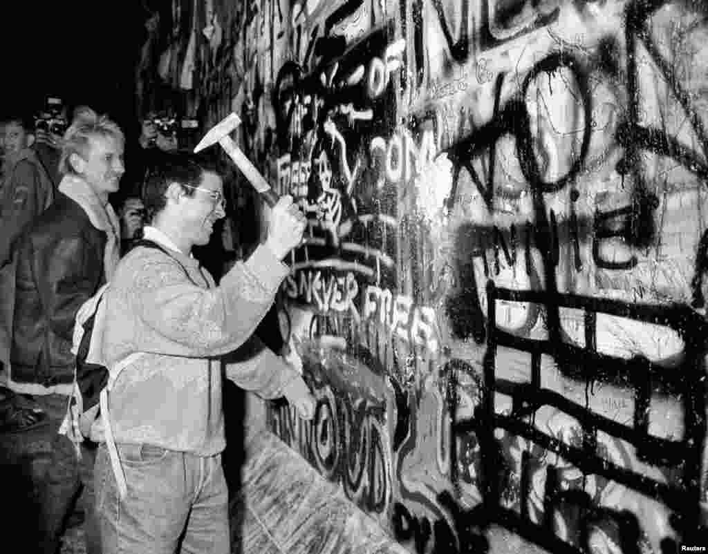 جرمنی کے تاریخی مقام 'برانڈنبرگ گیٹ' پر مشرقی جرمنی سے تعلق رکھنے والا ایک شخص ہتھوڑے سے دیوار مسمار کر رہا ہے۔