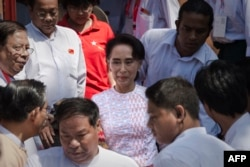 Myanmar opposition leader Aung San Suu Kyi, center, leaves the headquarters of the National League of Democracy (NLD) after she made a speech to a small crowd and the media in Yangon, Nov. 9, 2015.
