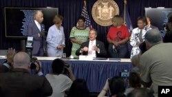 Guvernatori i Nju Jorkut nënshkruan ligjin në prani të Valerie Bell dhe Gwen Carr, nënat e Sean Bell dhe Eric Garner, dy njujorkezë që vdiqën gjatë incidenteve me policinë