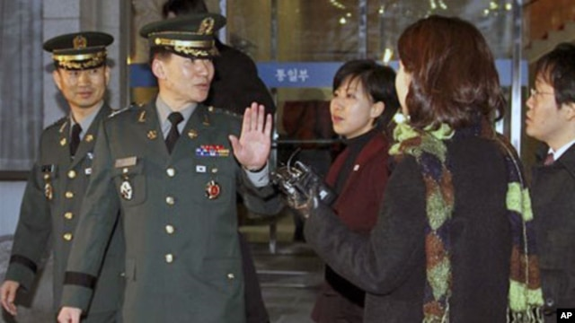 South Korean delegate Army Col. Moon Sang-gyun, second from left, is questioned by reporters as he leaves for military meeting with North Korea in Seoul, South Korea, February 8, 2011.