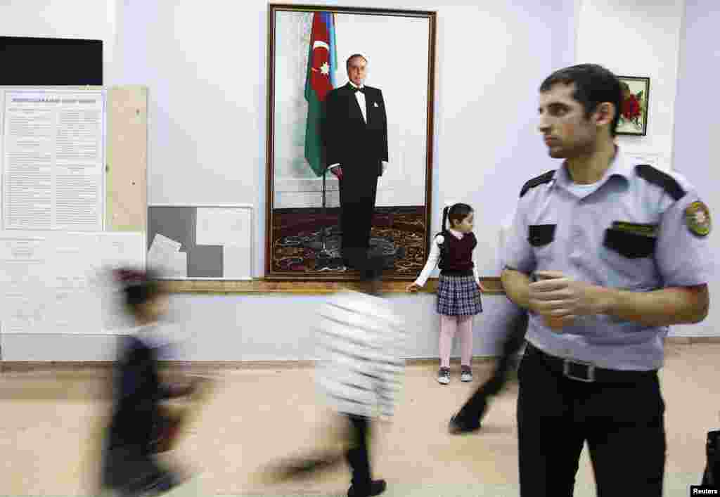 An election official looks on as children play in front of a portrait of Heydar Aliyev, Azerbaijan's late president and father of current President Ilham Aliyev, at a polling station in a school in Baku, Oct. 8, 2013.