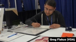 Houston high school teacher Eden Bautista sketched at his booth while waiting for people at Comicpalooza to stop by and check out his work, in Houston.