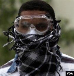 Seorang pemuda di Manama, Bahrain, siap menghadapi gas air mata yang sering digunakan aparat untuk membubarkan para demonstran.
