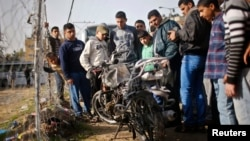 巴勒斯坦人觀看被以色列空襲損壞的摩托車