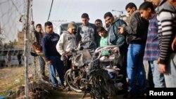 팔레스타인 주민들이 19일 이스라엘의 로켓 공습으로 파괴된 오토바이의 잔해더미를 지켜보고 있다