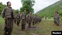 FILE - Kurdistan Workers Party (PKK) fighters stand at formation in northern Iraq, May 14, 2013.