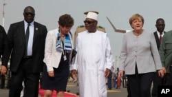 Le président malien Ibrahim Boubacar Keita (au centre) a accueilli la chancelière allemande Angela Merkel (à dr.) à l'arrivée de celle-ci à l'aéroport de Bamako, le 9 octobre 2016.