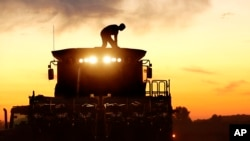 FILE - A corn farmer, on top of his combine, is silhouetted against the setting sun while harvesting corn in Pleasant Plains, Illinois, Sept. 27, 2014.