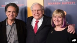 "FILE - In this Jan. 19, 2017 photo, Peter Buffett, from left, Warren Buffett and Susie Buffett attend the world premiere screening of HBO's ""Becoming Warren Buffett"" at The Museum of Modern Art in New York."