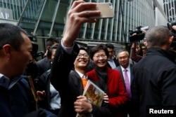 A man takes a selfie with Carrie Lam, chief executive-elect, a day after she was elected in Hong Kong, China, March 27, 2017.
