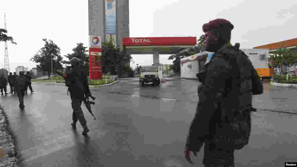 Congolese security forces secure the street near the state television headquarters in Kinshasa, Dec. 30, 2013.