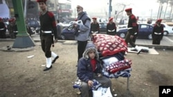 A boy waits with his belonging as Egyptian officers walk behind him, in Tahrir Square, in Cairo, Egypt, February 14, 2011