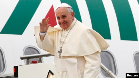 Pope Francis waves as he boards a plane at Fiumicino airport in Rome, November 28, 2014.