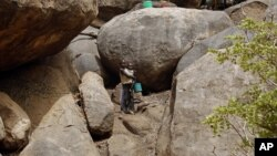 Children stand outside a cave shelter in Tess village in the rebel-held territory of the Nuba Mountains in South Kordofan May 2, 2012.