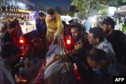 Relawan dan staf medis menurunkan mayat dari truk pickup di luar rumah sakit setelah dua ledakan kuat, yang menewaskan sedikitnya enam orang, di luar bandara di Kabul pada 26 Agustus 2021. (Foto: AFP)