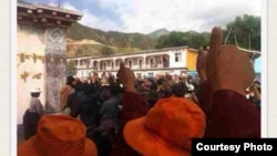 FILE - Tibetan protesters in Denma give the thumbs up sign during a protest in August.