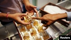 FILE - An employee shows gold bangles to a customer at a jewelry showroom on the occasion of Dhanteras, a Hindu festival associated with Lakshmi, the goddess of wealth, at a market in Mumbai, Nov. 1, 2013.