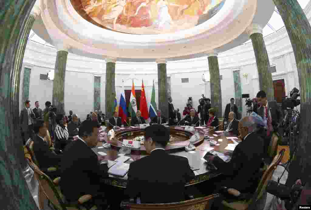 Participants sit at a table during a BRICS leaders' meeting at the G20 Summit in Strelna near St. Petersburg, Sept. 5, 2013.