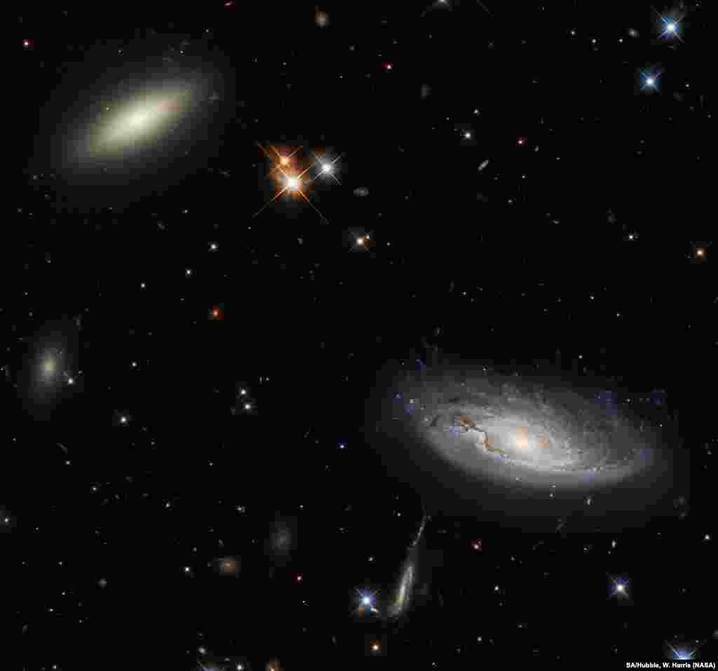 A lenticular galaxy, L, and the spiral galaxy named UGC 2665, R, lie approximately 350 million light-years from Earth. They both form part of the enormous Perseus galaxy cluster.