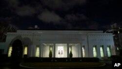 Jendela-jendela di Sayap Barat Gedung Putih, Washington D.C. tampak terang nyala lampu setelah berita serangan rudal terhadap pangkalan Irak yang juga menjadi pangkalan pasukan AS, di Irak, Selasa, 7 Januari 2020. (Foto: AP)