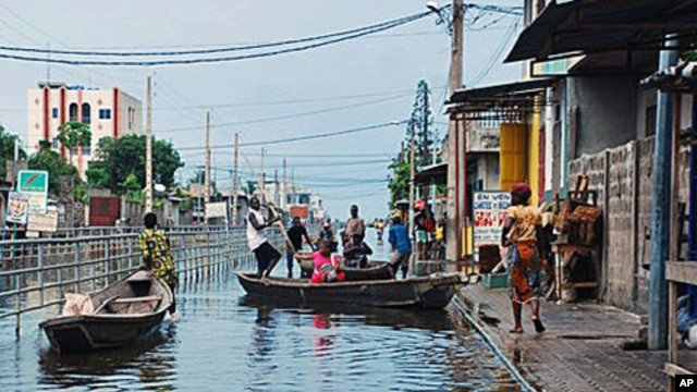 Residents board canoes in a city street flooded by an overflowing drainage canal, in the Saint Martin neighborhood of Cotonou, Benin, 9 Oct 2010