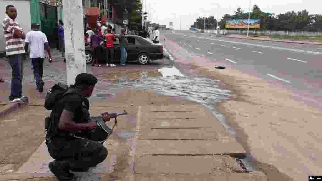 Un agent des forces de l'ordre prend position, arme à la main et prête à être utilisée, lors d'une émeute à Kinshasa prêt de la télévision nationale congolaise, le 30 décembre 2013. REUTERS/Jean Robert N'Kengo.
