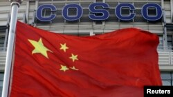 A Chinese national flag flies in front of COSCO's headquarters in Beijing, August 26, 2010.