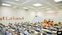 A class of 31 boys receives instruction at the Hsi Lai Temple in Los Angeles, California, with their heads temporarily shaved as monks, in a retreat to introduce them more deeply to Buddhist life before they return to their regular lives, July 2011