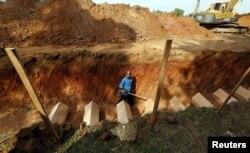 ຊາຍຄົນນຶ່ງ ຍ່າງຢູ່ໃນຂຸມຝັງສົບ ທີ່ເຕັມໄປດ້ວຍ ຫີບສົບຂອງພວກຊາວ Rohingya ທີ່ໄດ້ຖືກພົບເຫັນຢູ່ໃນຄ້າຍ Wang Kelian ຂອງພວກລັກລອບຄ້າມະນຸດ, ຢູ່ປ່າຊ້າ ໃກ້ໆກັບ ເມືອງ Alor Setar ຂອງມາເລເຊຍ.