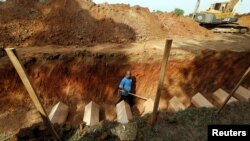 A man walks in a mass grave amongst coffins of unidentified remains of Rohingya people found at a traffickers camp in Wang Kelian last month, at a cemetery near Alor Setar, Malaysia, June 22, 2015.