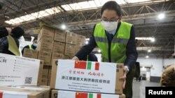 Nhân viên khuân các thùng vật tư y tế của Trung Quốc gửi cho Ý để ngăn dịch virus corona lây lan, tại một trung tâm logistics của sân bay quốc tế Hàng Châu, tỉnh Chiết Giang, ngày 10 tháng 3, 2020.