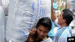 Laborers carry large bags of goods while working at a market in Bangkok, January 4, 2013. Thailand's new daily minimum wage hike to 300 baht ($9.8 USD) went into effect throughout the country January 1, 2013.