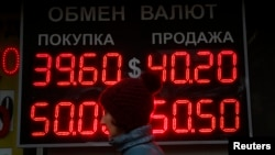 A woman passes by a board showing currency exchange rates in Moscow, Oct. 6, 2014.