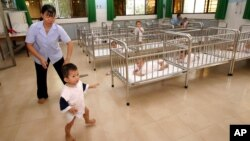 In this 2007 file photo, a staff member follows an orphan at the Tam Binh 1 Orphanage in Ho Chi Minh City.