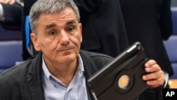 FILE - Greece's Finance Minister Euclid Tsakalotos prepares for a Eurogroup meeting at the EU Council in Luxembourg, Oct. 10, 2016.