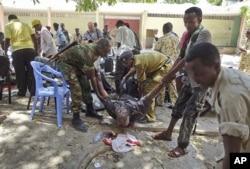 Des Somaliens aidant un blessé après l'explosion du 4 avril 2012 au Théâtre national
