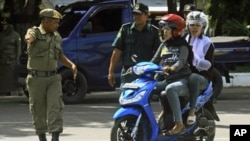 A local security personnel and a Sharia policeman stop women who flout the province's dress code by wearing tight pants during a street inspection in Banda, Aceh, June 9, 2011.