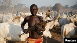 A man from Dinka tribe holds his rifle in front of cows in a Dinka cattle herders camp in central South Sudan, December 14, 2013. (REUTERS/Goran Tomasevic)