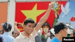 A protester gestures as he marches during an anti-China protest in Vietnam's southern Ho Chi Minh city May 18, 2014. Vietnam flooded major cities with police to avert anti-China protests on Sunday in the wake of rare and deadly rioting in industrial parks