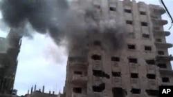 시리아 정부군의 포격으로 반군 거점 지역인 홈즈시의 한 건물에서 검은 연기가 치솟고 있다.