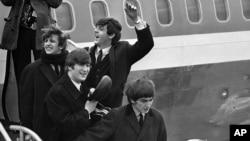 ພາບຂອງວົງດົນຕີ The Beatles, ຈາກຊ້າຍ, ຣິງໂກ ສຕາຣ໌ (Ringo Starr), ຈອນ ເລັນນັອນ (John Lennon), ພອລ ເມັກຄາຕີ (Paul McCartney) ແລະ ຈອຈ (George) ເດີນທາງມາຮອດສະໜາມບິນ ຈອນ ແອັຟ ເຄັນເນີດີ (John F. Kennedy) ທີ່ນະຄອນ ນິວຢອກ ໃນວັນທີ 7 ກຸມພາ 1964.