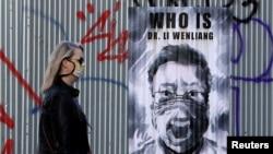 一名領導人口罩的捷克女子走過布拉格街頭一幅中國眼科醫生李文亮的遺像。(2020年3月27日)