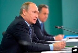 Russian President Vladimir Putin, left, and Sports Minister Vitaly Mutko, attend their late-night meeting with the heads of Russia's sports federations in the Black Sea resort of Sochi, Russia, Wednesday, Nov. 11, 2015.