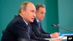 Le président russe Vladimir Poutine, à gauche, et le ministre des Sports, Vitaly Mutko, assistent à une réunion avec les chefs des fédérations sportives de la Russie dans la station balnéaire de la mer Noire de Sotchi, en Russie, 11 novembre 2015.